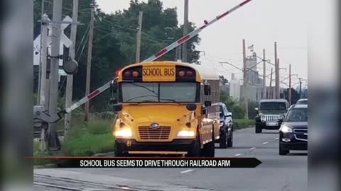 South Bend School bus stops under railroad crossing arm
